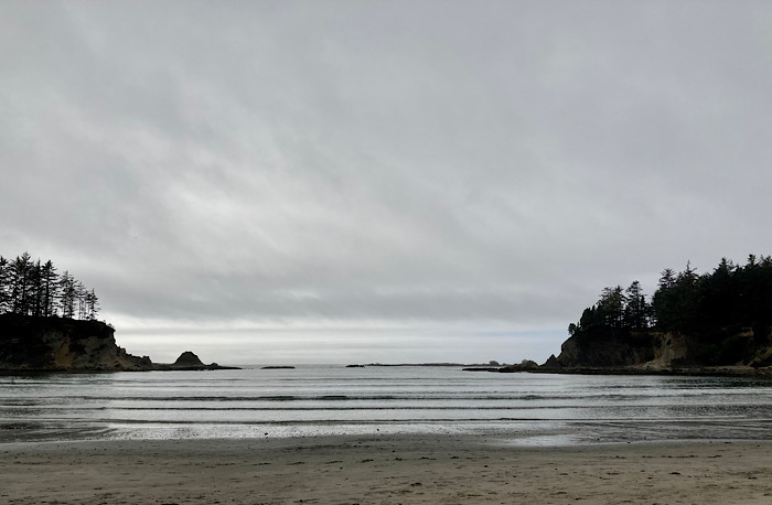 Overcast sky and gradually sloped, calm sea good for swimming, protected by forested points.