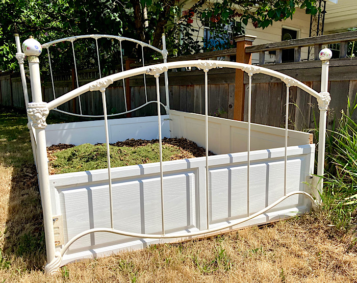 Four-poster bed frame sitting on a lawn, partially filled with dirt/compost.