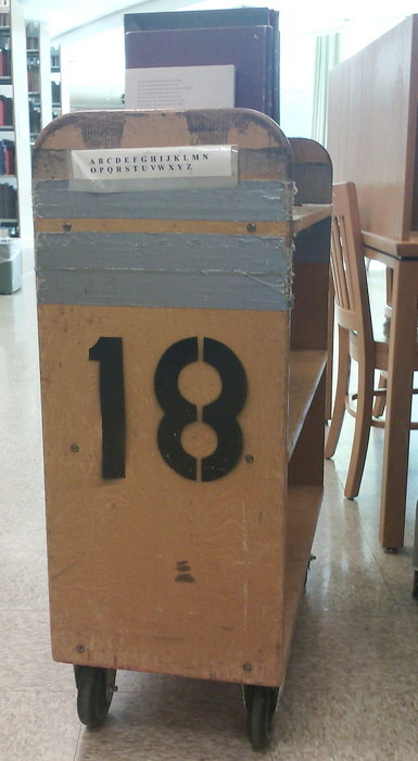 wooden library shelving cart with a stenciled 18 and a taped-on printout of the alphabet in capital letters