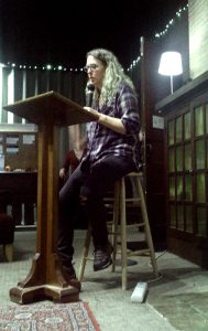 author A.S. King in flannel and jeans, reading at a lectern