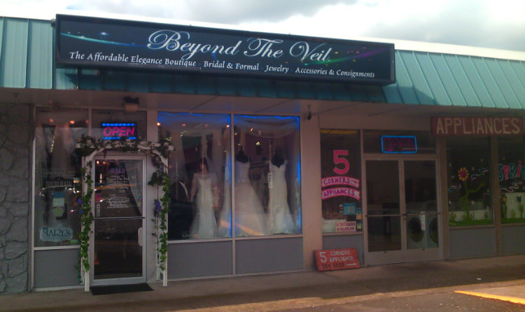 strip mall storefront: Beyond the Veil bridal shop with arch at doorway and mannequins in window