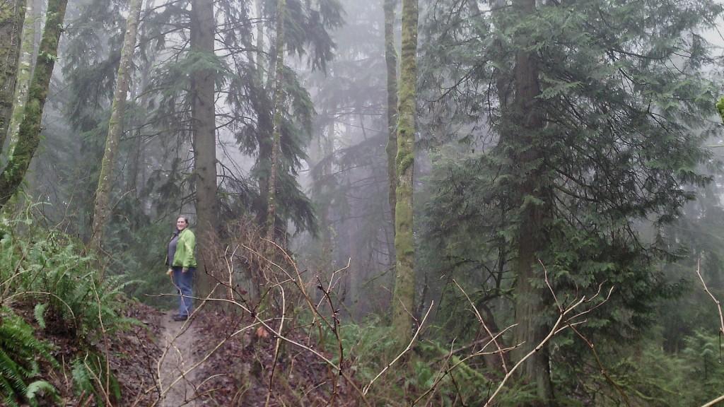 Elizabeth on a trail with big woods all around
