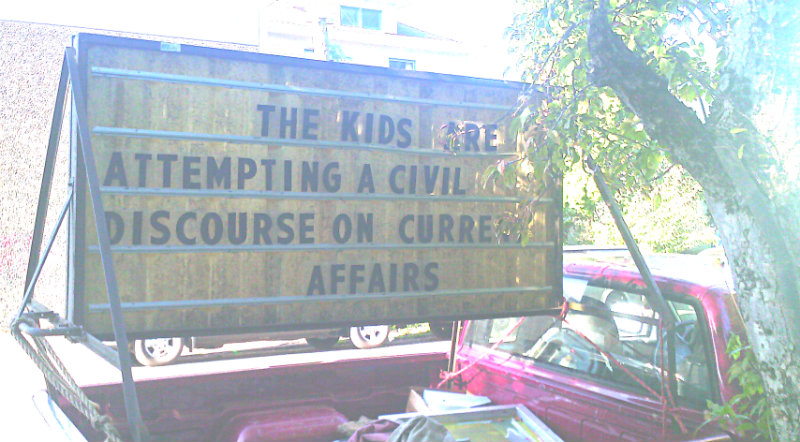 sign in pickup bed reads THE KIDS ARE ATTEMPTING A CIVIL DISCOURSE ON CURRENT AFFAIRS