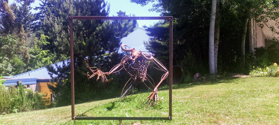 sculpture of monster reaching through a metal square frame