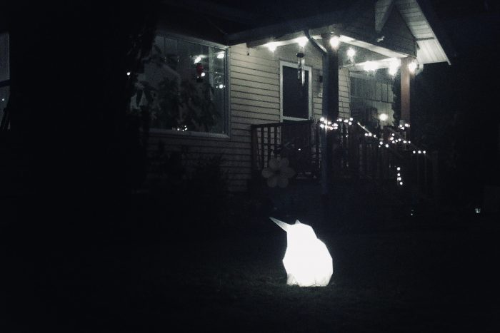 Glowing origami-style rabbit on a nighttime lawn with house in background