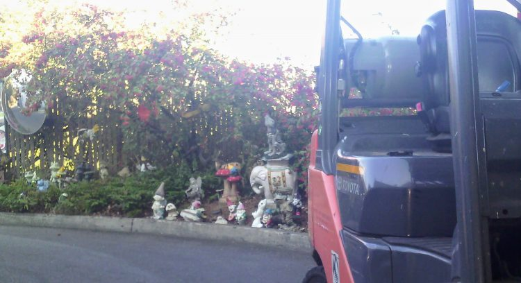 View past a forklift to a collection of garden gnomes and similar statues by a curb