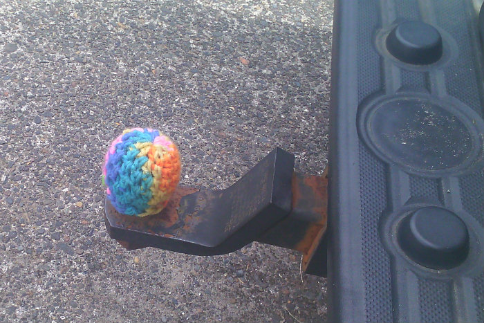 a trailer hitch with a knitted cozy in rainbow colors
