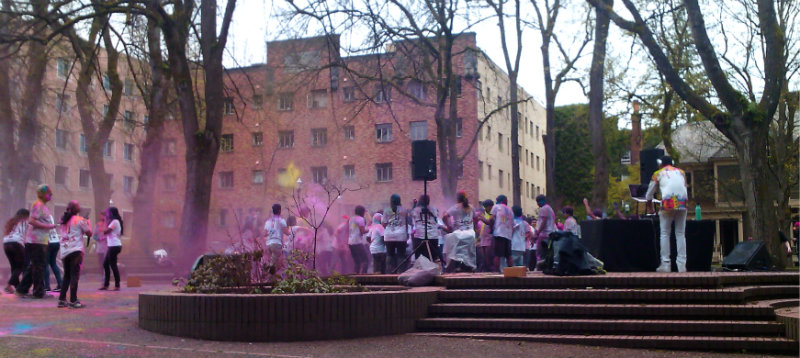 DJ and people in white t-shirts dancing amid colored powders in the air, in campus plaza