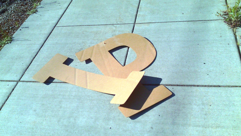 cardboard letters on sidewalk I P