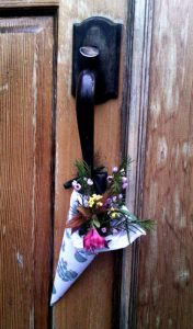 wooden door at Taborspace with a conical May basket tied to the latch