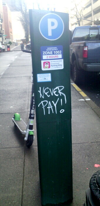 "parking meter with graffiti ""NEVER PAY!"""