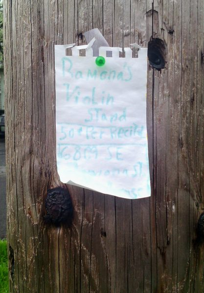 Handwritten sign pinned to telephone pole