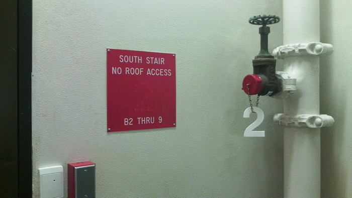 in a stairwell, the plastic 2 designating 2nd floor has fallen off its sign and been hung from a chain on a pipe valve