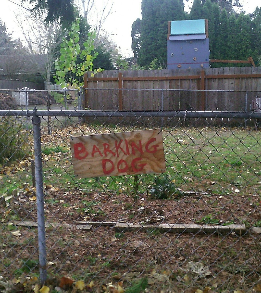 sign on fence: BARKING DOG