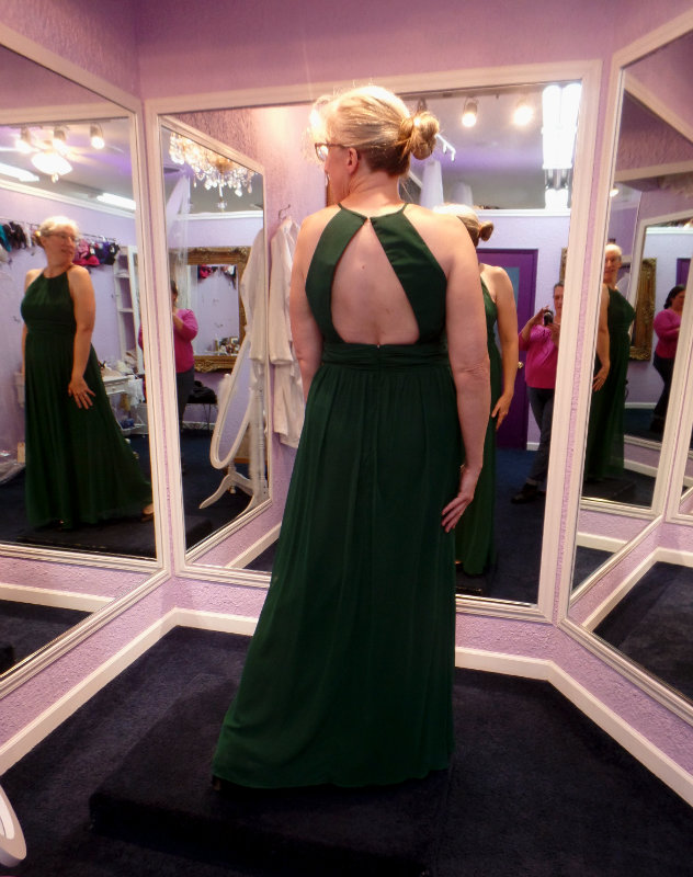 Holly in a full-length halter-top dress, from the back and seen in a 3-way mirror in a fitting room