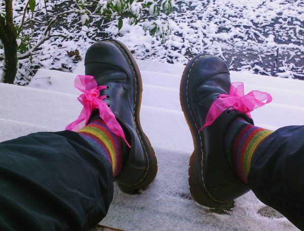 feet wearing doc martens with pink chiffon shoelaces, and stripey socks, against a snowy background