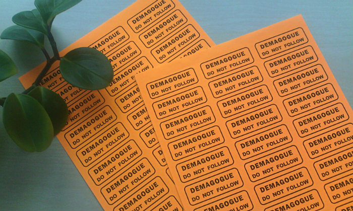 "two sheets of orange mailing labels that read ""DEMAGOGUE / DO NOT FOLLOW"""
